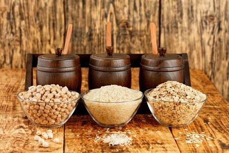 Chickpeas, rice and oatmeal in glass bowls against the background of small wooden barrels for storing bulk products on an old wooden table against on wooden background, copy space.