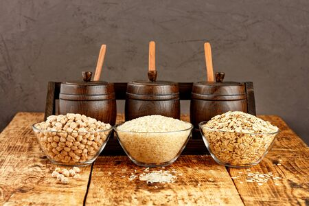 Chickpeas, rice and oatmeal in glass bowls against the background of small wooden barrels for storing bulk products on an old wooden table against on brown background, copy space. 免版税图像