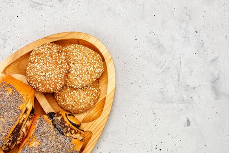 Homemade fresh buns with poppy seeds and cookies with sesame seeds on a wooden kitchen board, on a background of gray concrete, closeup, copy space.