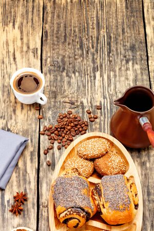 Coffee beans are scattered on an old wooden table and freshly brewed coffee in a white porcelain cup to anise stars, next to a coffee teapot and homemade fresh buns in slight blur.