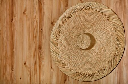 A large beautiful round sambrero hat made of rattan hanging on the background of a natural wooden wall.