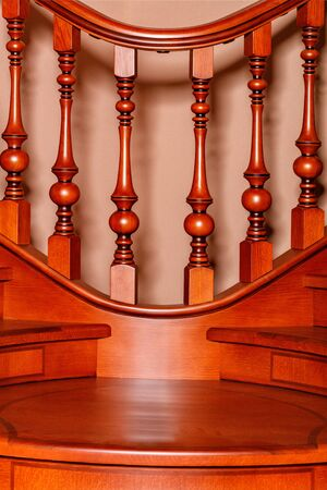 Fragment beautiful of a wooden staircase with figured carved balusters and railings and tinted mahogany.