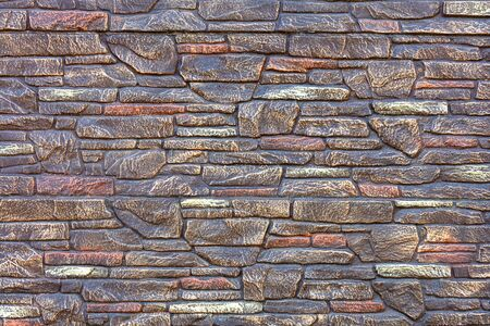 Old monolithic and cracked stone in a mosaic, with spots of bronze, gray and brown in the wall with concrete as background.