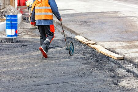An engineer measuring road distances with a measuring wheel determines the required amount of asphalt for laying on a new section of the road.