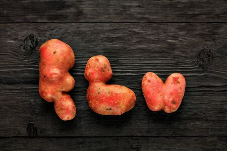 Ugly funny vegetables, heart-shaped potatoes and letter-shaped potatoes, black wooden background. The concept of grungy vegetables or food waste. Flat lay, copy space.