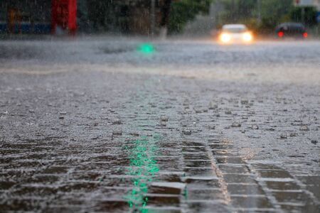 Heavy rain on the sidewalk and asphalt road is illuminated by the headlights of the car and the reflection of the green traffic light.