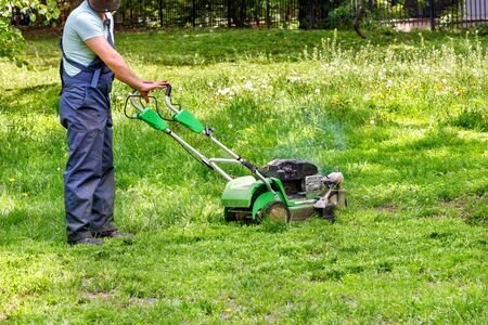 A utility worker in blue overalls looks after a green lawn with a petrol lawnmower. Imagens