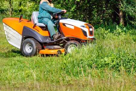 A gardener mows tall green grass in an overgrown meadow with a professional lawnmower on a clear sunny day, copy space.