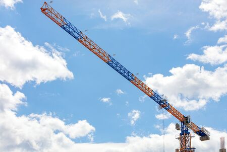 The arrow of a high-rise construction crane on   blue sky and white clouds