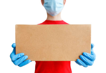 Courier delivery service with a cardboard box in hands. A man in a medical mask and rubber gloves, in a red T-shirt on a white isolated background, shallow depth of field, selective focus.
