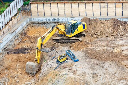 A large excavator digs a pit at a new construction site, an angle view from a height. Reklamní fotografie