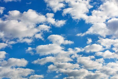 White fluffy clouds float high above your head in backlight. Banco de Imagens