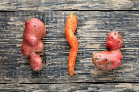 Ugly funny vegetables, letter-shaped potatoes and twisted carrots on a weathered wooden background. The concept of grungy vegetables or food waste. Top view, copy space.
