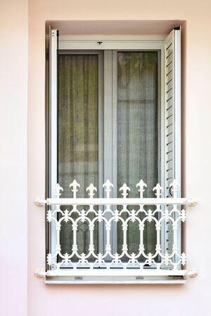 Modern metal-plastic transparent balcony window doors with lattice shutters with metal decorative figured lattice of the balcony, framed in the Greek style. Banco de Imagens