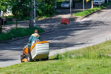 A utility worker takes care of roadside lawns, mowing tall grass with a professional lawnmower, image with copy space. Banco de Imagens