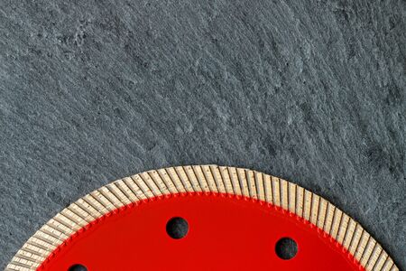 The red diamond cutting professional circle segment with a thin blade and flange is used for precise cutting of material against a gray granite background, image with copy space.