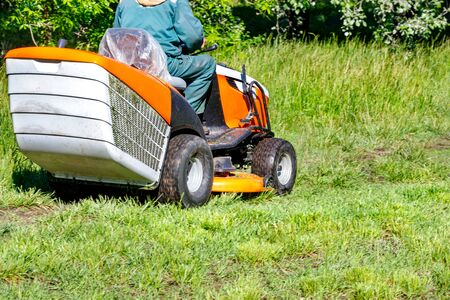 A well-kept park with a trimmed lawn as a result of a gardener working with a professional tractor lawn mower on a clear sunny day. Banco de Imagens