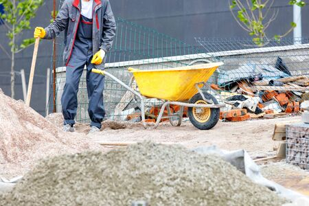 A worker in blue overalls stands near a pile of sand and a yellow construction wheelbarrow against the background of a construction workplace, image with copy space.