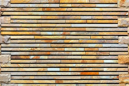 The texture and frame of the stone wall made of pieces of processed flat gold sandstone.