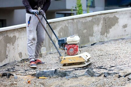 A road service worker uses a petrol plate compacting crushed stone at a road repair site.