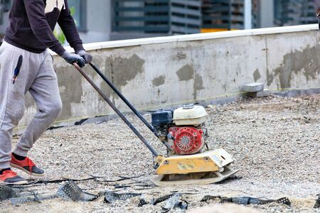 A road worker uses a gasoline stove to compact crushed stone at the site of road repair and subsequent laying of paving slabs. Banco de Imagens