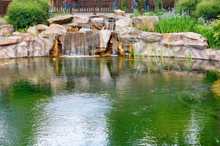 Reflection of the sky and greenery in the pond of a city park, a decorative waterfall pours between large stone boulders, copy space.