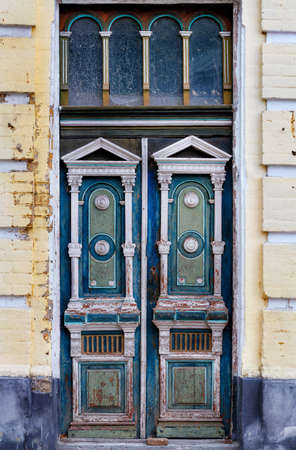 Old tall wooden entrance doors in blue and white colors with carved elements are framed on the facade of an old house with a carved symmetrical pattern.