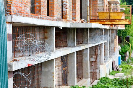 Barbed wire and rusty iron rods prevent entry into an abandoned construction site in the industrial zone.