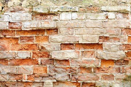Old ruined red brick wall with cracked and broken bricks. Background texture of debris and piece of brickwork.