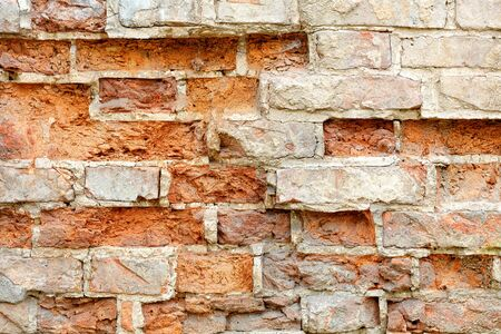 Background texture and piece of brickwork. Old ruined red brick wall with cracked and broken bricks, image with copy space. Standard-Bild