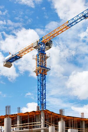 The arrow of a yellow and blue high-rise tower crane rises above the construction site diagonally against a background of blue sky and white clouds, copy space. Standard-Bild