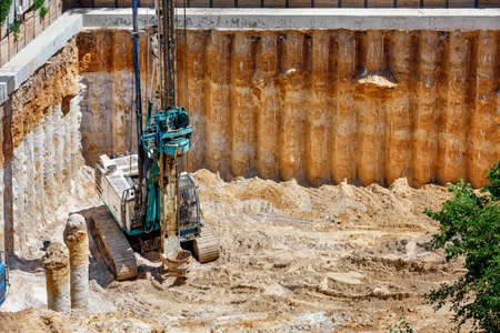 A large excavator installs concrete columns of drilling rig to strengthen the foundation of the future high-rise building, a viewing angle from a height, copy space. Standard-Bild