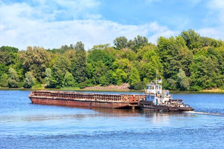 River tugboat pushes an empty rusty barge along the river against the background of coastal greenery and calm surface of the water, the concept of river freight transportation, copy space. Standard-Bild
