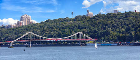 Pedestrian bridge in Kyiv, view panorama of the city of Kyiv, on Dnipro river, sailboat, Ukraine. Standard-Bild