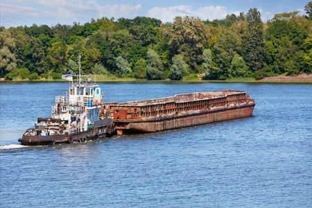River tugboat pushes an empty rusty barge across a wide river to the other bank against the backdrop of coastal greenery and a calm surface of the water, the concept of river freight transport, copy space.