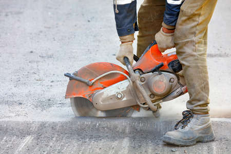 A worker mends part of the road, cuts out worn asphalt in a cloud of dust using a portable concrete cutter and a cutting diamond blade, copy space, close-up.