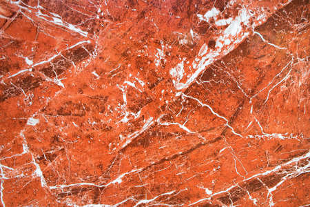 Amazing fiery view on a background of red granite stone with white veins. The surface of natural red granite, polished crystalline and texture, mineral stone closeup, macro.
