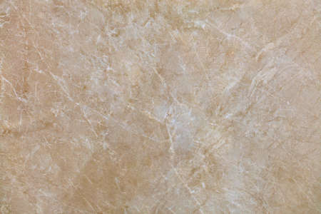 Unusual texture of old beige marble with whitish beige spots, cracks and scratches. Polished surface.