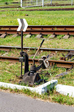 Vintage manual translator of railway arrows. The mechanism of the railway switch on the background of railway tracks and green grass on a sunny day. Standard-Bild