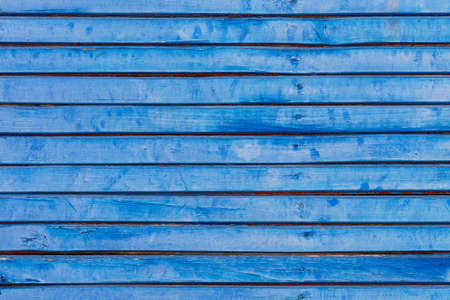 Fence from an old lining board clapboard covered with blue paint with a weathered cracked surface.