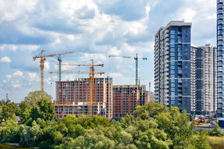 Construction site of a multi-storey residential complex on the river bank against the background of coastal trees, cloudy sky and facades of new buildings, copy space. Standard-Bild