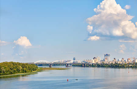 Over the water surface of the wide Dnipro River, large figured cloud illuminated by sunlight floated in the blue sky, skirting the white railway bridge and new residential quarters of Kyiv, copy space. Standard-Bild