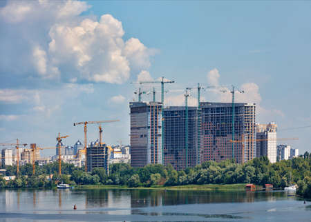 Construction site on the river bank, facades of high-rise residential buildings under construction with tower cranes against the background of a blue cloudy sky, copy space.