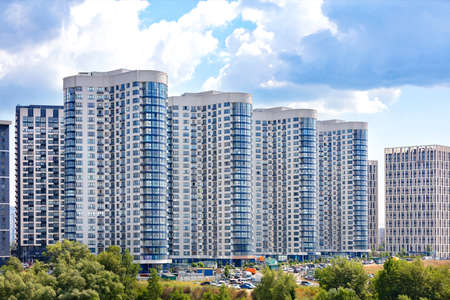 White and blue facades of new residential high-rise buildings in a residential area of the city against a blue cloudy sky.