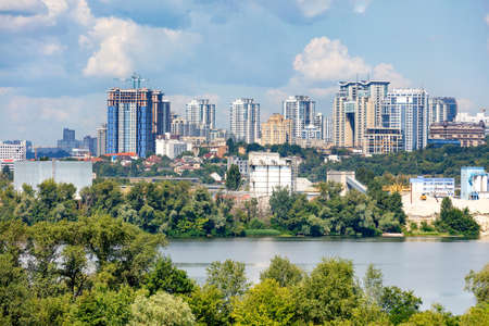 Construction of new high-rise buildings on the right bank of the Dnipro River in Kyiv, a view of the facades of multi-storey residential buildings among private houses and a blue cloudy sky, copy space.