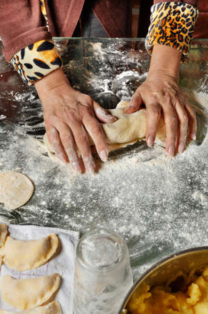 Women's hands knead dough with their hands on a glass table and prepare delicious and hearty vareniki with potatoes. Ukrainian national cuisine, close-up, copy space.