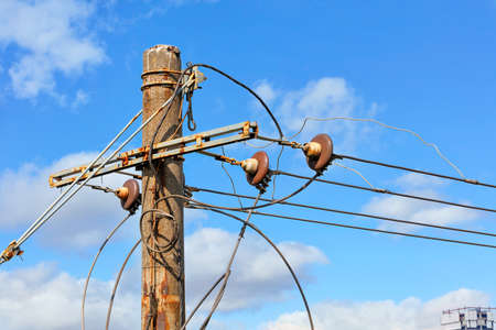 The top of an old concrete pillar with electric wires and a connected three-phase current stands against a blue cloudy sky.