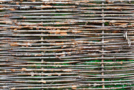 Texture and background of a wicker fence made of old weathered branches, copy space. Standard-Bild