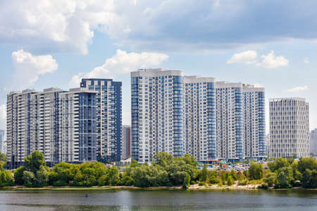 White and blue cascading facades of new residential multi-storey buildings in a residential area of the city on the river bank against a blue cloudy sky.
