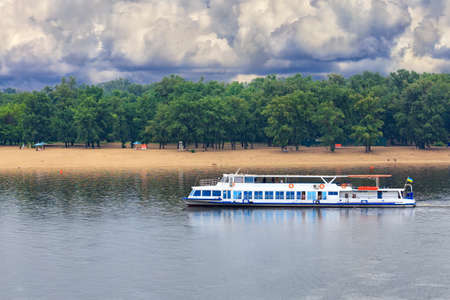 A river tram with a few tourists resting goes along the river against the backdrop of coastal greenery, storm sky and a deserted beach in anticipation of an impending thunderstorm. River passenger transport, concept, copy space.